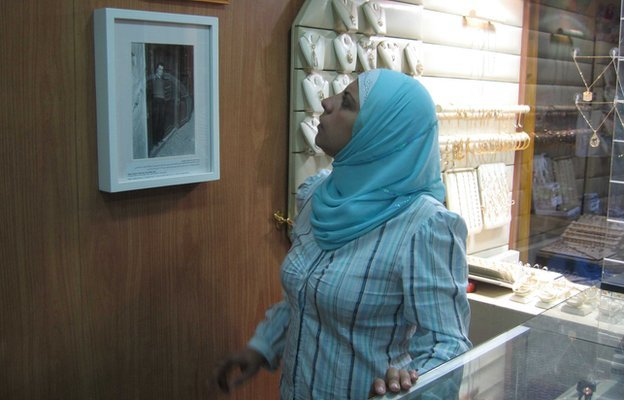 A Saida jeweller looks at Madani's historic photo of her shop.