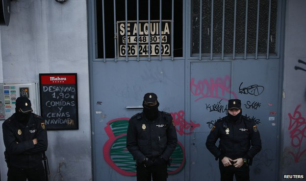 Police outside a home as they wait to carry out an eviction in Madrid December 11, 2013.