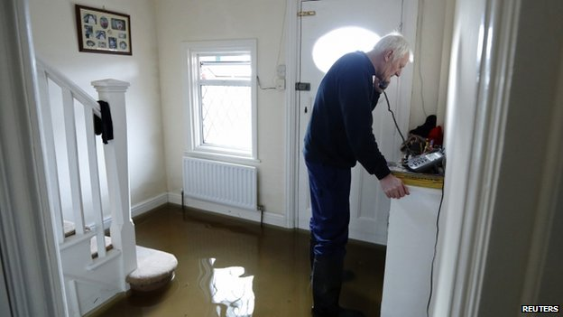 Michael Simmonds speaks on the phone in his flooded home at Egham