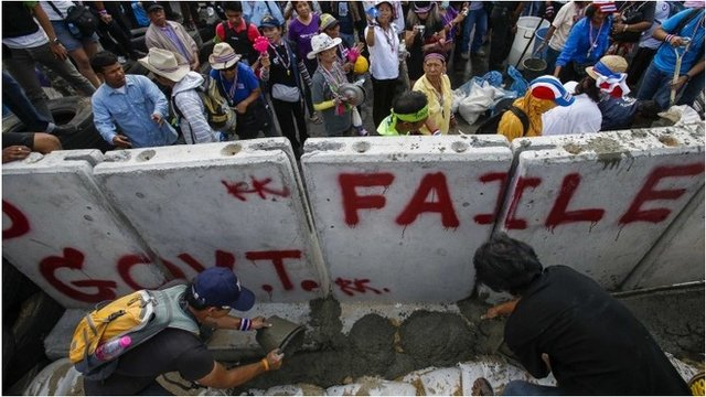 Anti-government protesters pour cement near a concrete wall set up to block a gate of the Government House during a rally in Bangkok