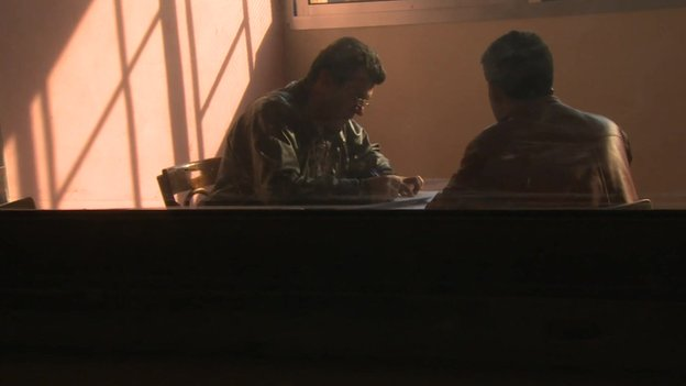 Two men talking inside a classroom at Homs detention centre