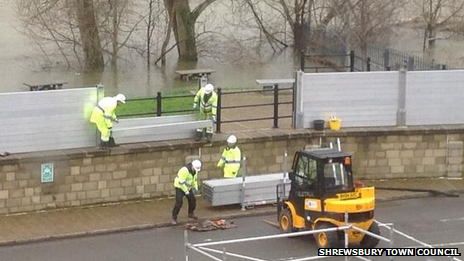 Workers take down some the the flood barriers in Frankwell