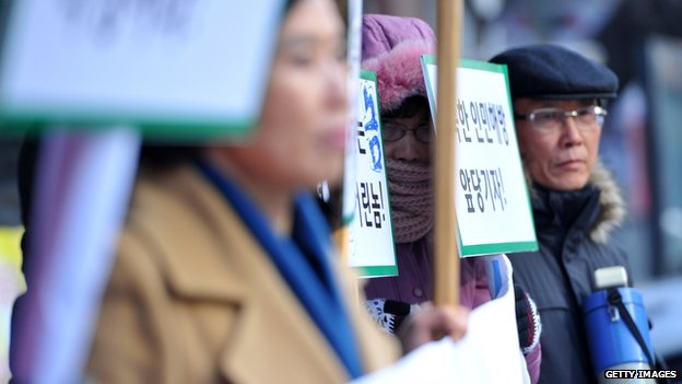 A member of the North Korean Defectors Association hides her face behind a slogan picket during a protest against North Korean leader Kim Jong-un's human rights abuses on second anniversary of the death of longtime leader Kim Jong-il in Seoul on 7 December 2013.