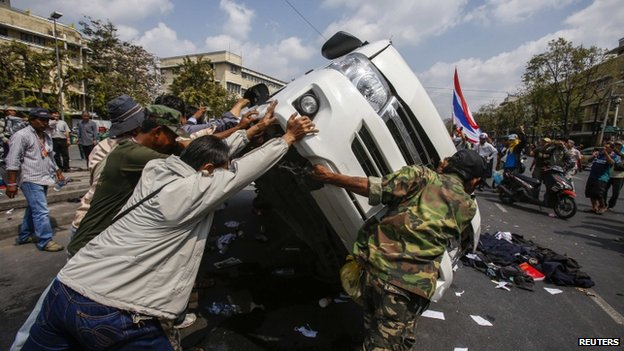 Anti-government protesters lift a police car after clashes with Thai riot police officers near Government House in Bangkok, 18 February 2014