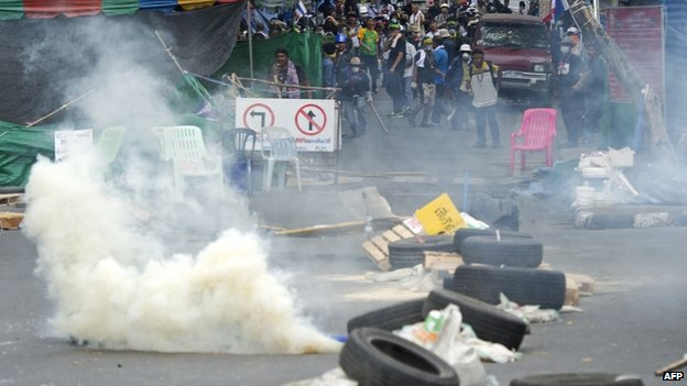 Thai anti-government protesters run from tear gas after police demanded they leave the area around the Government House in Bangkok on 18 February 2014
