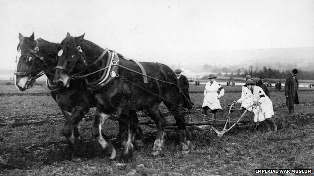 Members of the Women's Land Army operate a horse-drawn plough during World War One.