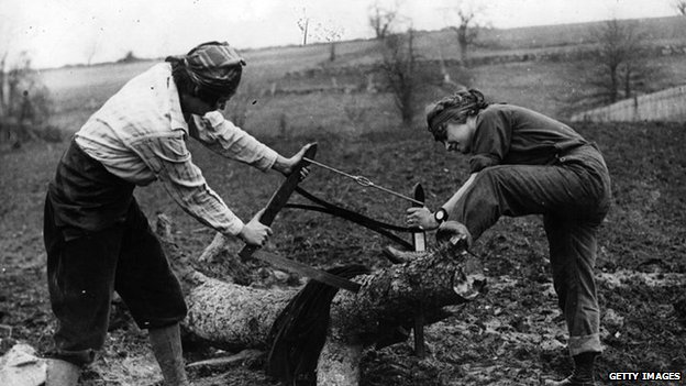 two land girls sawing a log