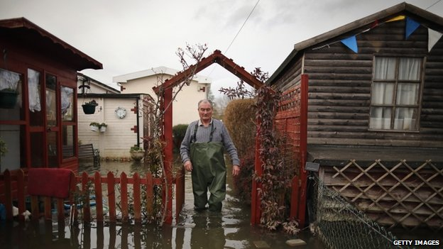 A man walking across a flooded garden in Chertsey, Surrey