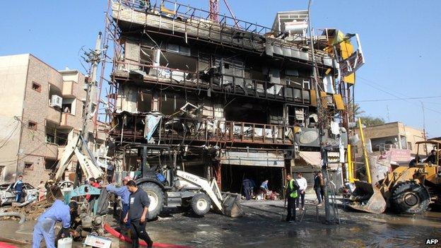 Municipality workers clean the area in the aftermath of an explosion in the Karrada commercial district in Baghdad