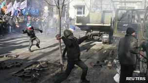 Anti-government protesters throw stones towards police during a rally near Ukraine's house of parliament in Kiev