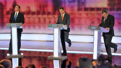 David Cameron, Nick Clegg and Gordon Brown at a 2010 election debate; Clegg and Brown both have their left legs flicked up as if in synch