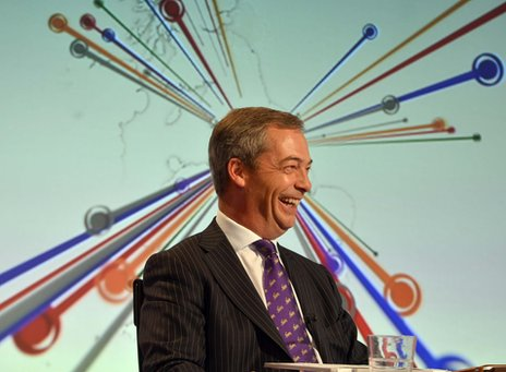 Nigel Farage smiling with a backdrop that makes it look as if many colours are coming out of his head in all directions