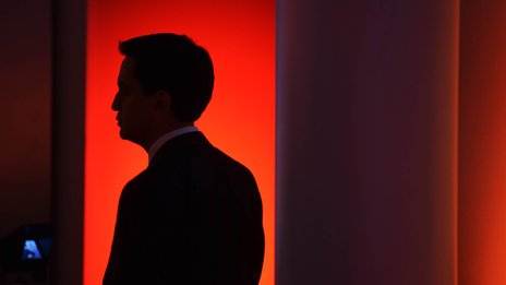 Ed Miliband in silhouette against a red light