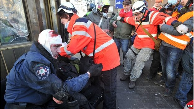 Red Cross workers help an injured policeman in Kiev, Ukraine (18 Feb 2014)