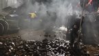 Anti-government protesters throw stones towards police during a rally in Kiev