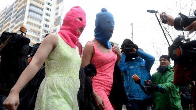 Wearing masks members of Russian punk group Pussy Riot, Nadezhda Tolokonnikova (C) and Maria Alyokhina (L)