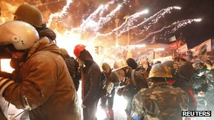 Fireworks explode near anti-government protesters during clashes with riot police at the Independence Square in Kiev, on 18 February 2014