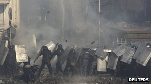 Riot police protect themselves from a hail of rocks thrown by protesters