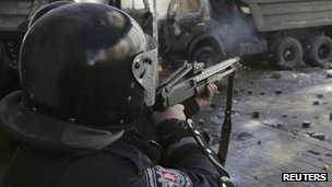 A police officer aims his rifle at protesters