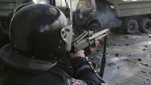 An Interior ministry member aims with his rifle during clashes with anti-government protesters