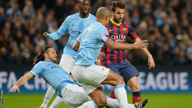Three Man City players attempt to tackle Cesc Fabregas