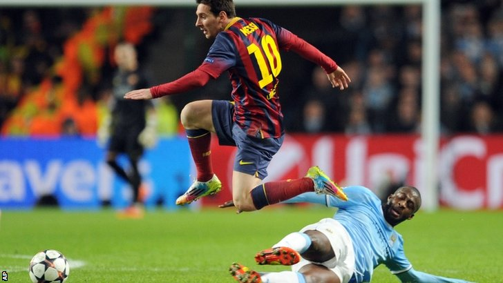 Yaya Toure attempts to tackle Lionel Messi