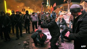 Anti-government protesters tear up paving stones to throw at police in Kiev on 18 February 2014.