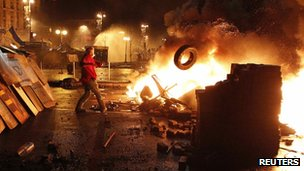An anti-government protester throws a tyre in a burning barricade in Kiev