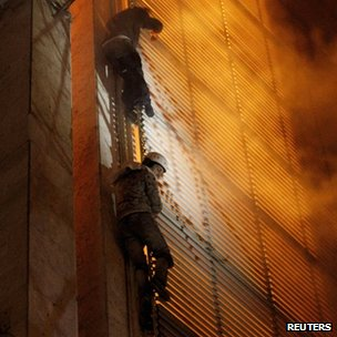 Activists try do escape from a burning building in Kiev
