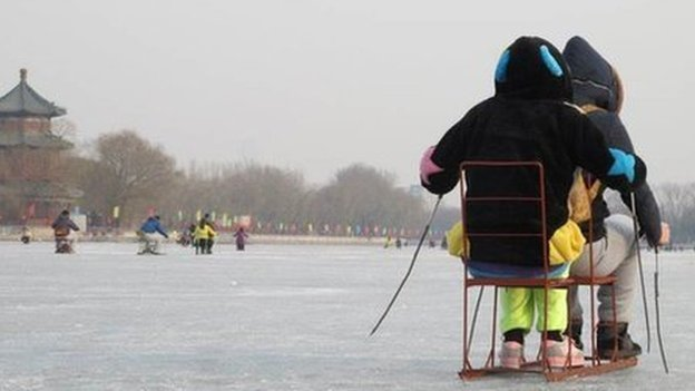 Chinese visitors sled across a lake in Beijing