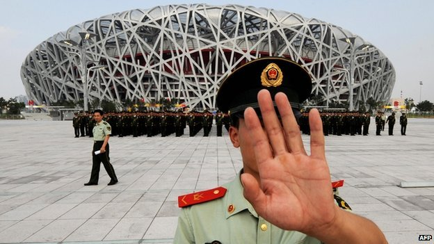 A Chinese paramilitary policeman tries to block photos being taken of a military parade rehearsal, outside the Olympic Stadium in Beijing on 21 July  2008
