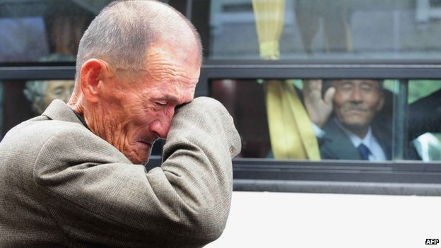 This file photo taken on 31 October 2010 shows an elderly South Korean man wiping his tears as a North Korean relative (in the bus) waves to say good-bye after a luncheon during a separated family reunion meeting