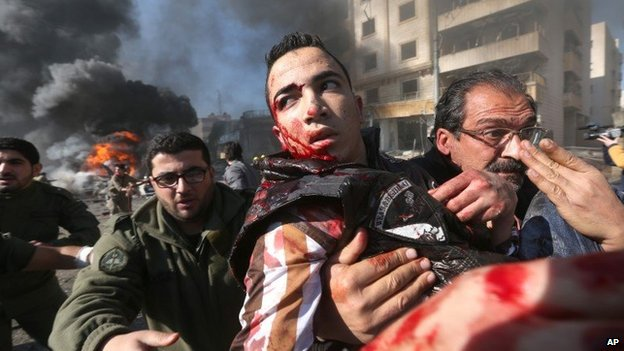 A wounded Lebanese man is helped away from the site of a bomb attack in Beirut (19 February 2014)