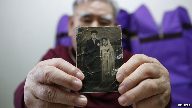 Jang Choon poses for photographs with a picture of his youngest brother Jang Ha-choon in Namyangju, east of Seoul, 19 February 2014