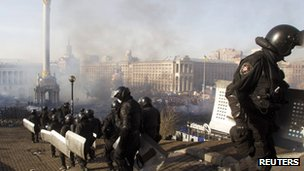 Interior Ministry officers walk in formation as smoke rises above Independence Square in Kiev