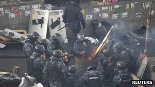 Riot police officers rest around a fire near Independence Square, Kiev.