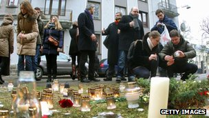 People lay down flowers and light candles in front of the Ukrainian embassy in Vilnius, Lithuania