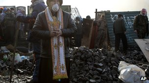 "An Orthodox priest stands at the barricades during clashes with riot police in Kiev""s Independence Square"