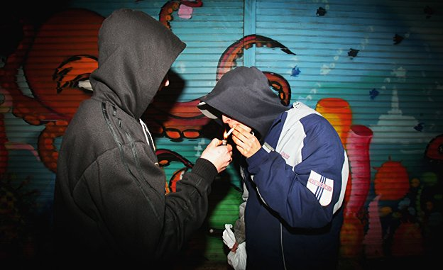 Two youths in hoodies are lighting a cigarette
