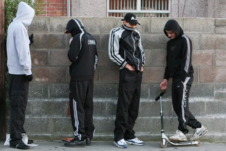 Four male teenagers standing against a wall with hoods on
