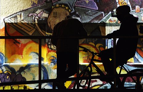 Two youths in hoodies are in silhouette against a graffiti backdrop
