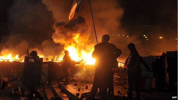 Anti-government protesters burn fires during clashes with the police during their storming of Independence Square in Kiev