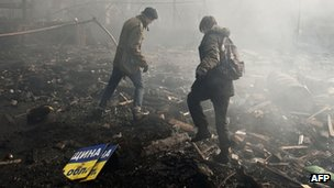 Anti-government protesters walk in the rubble on Kiev's Independence Square