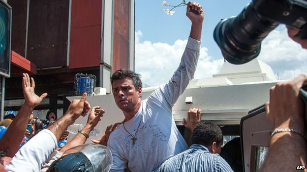 Leopoldo Lopez is escorted by the National Guard into a vehicle after he turned himself in