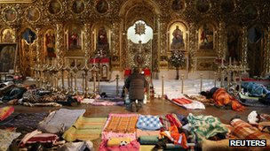 A man (C) prays as people rest inside Mikhailovsky Zlatoverkhy Cathedral which serves as a temporary shelter and a first-aid post for anti-government protesters, in Kiev on 19 February 2014.
