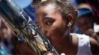 A young girl kisses the baton as the journey prepare to depart South Africa.