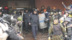 Interior ministry members leave the building as anti-government protesters hold a rally outside an office of the interior ministry in the town of Lutsk in north-western Ukraine, on 19 February 2014.