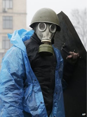 An anti-government protester stands behind a barricade during clashes with riot police in Kiev's Independence Square