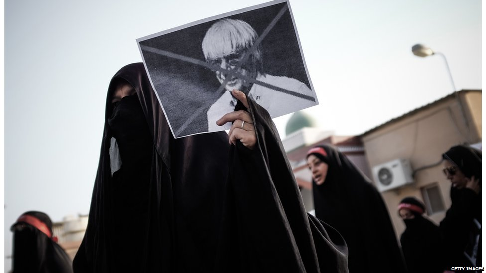 A Bahraini woman holds a cross marked picture of Formula One boss, Bernie Ecclestone, during a protest against the upcoming Bahrain Formula One Grand Prix