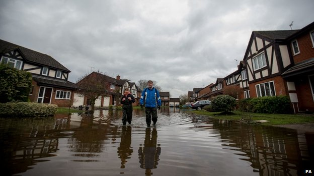 John Matthews and Sally De'Ath walk make their way through floodwater in Staines-upon-Thames, Surrey
